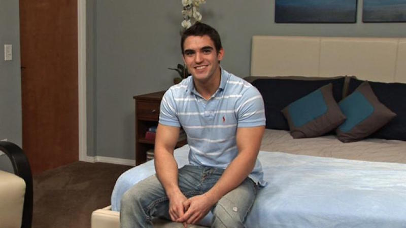 handsome jock sitting on a bed in a jerk off video