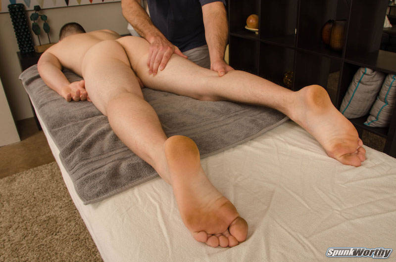 naked straight man face down on a massage table and being massaged by another man