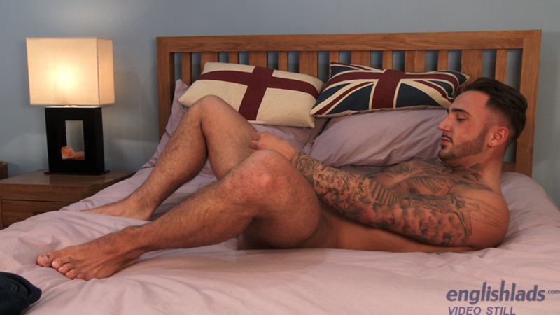 straight jock laying back on a bed and wanking his cock