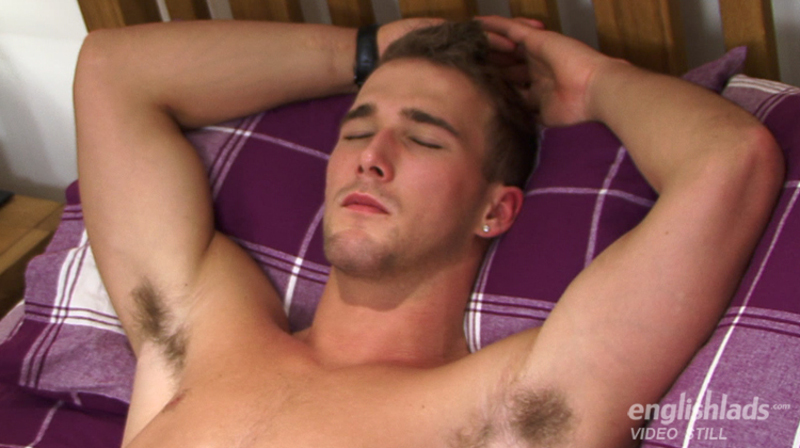 gorgeous straight guy laying back on a bed with his eyes closed while another man strokes his uncut cock