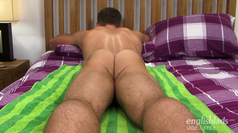naked straight jock face down on a bed while being massaged in a hand job video