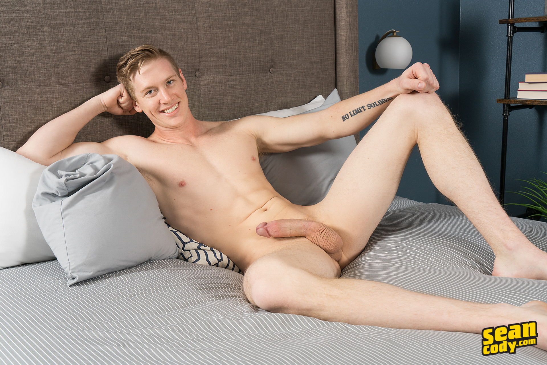 Naked jock reclines on a bed with his long cock hard
