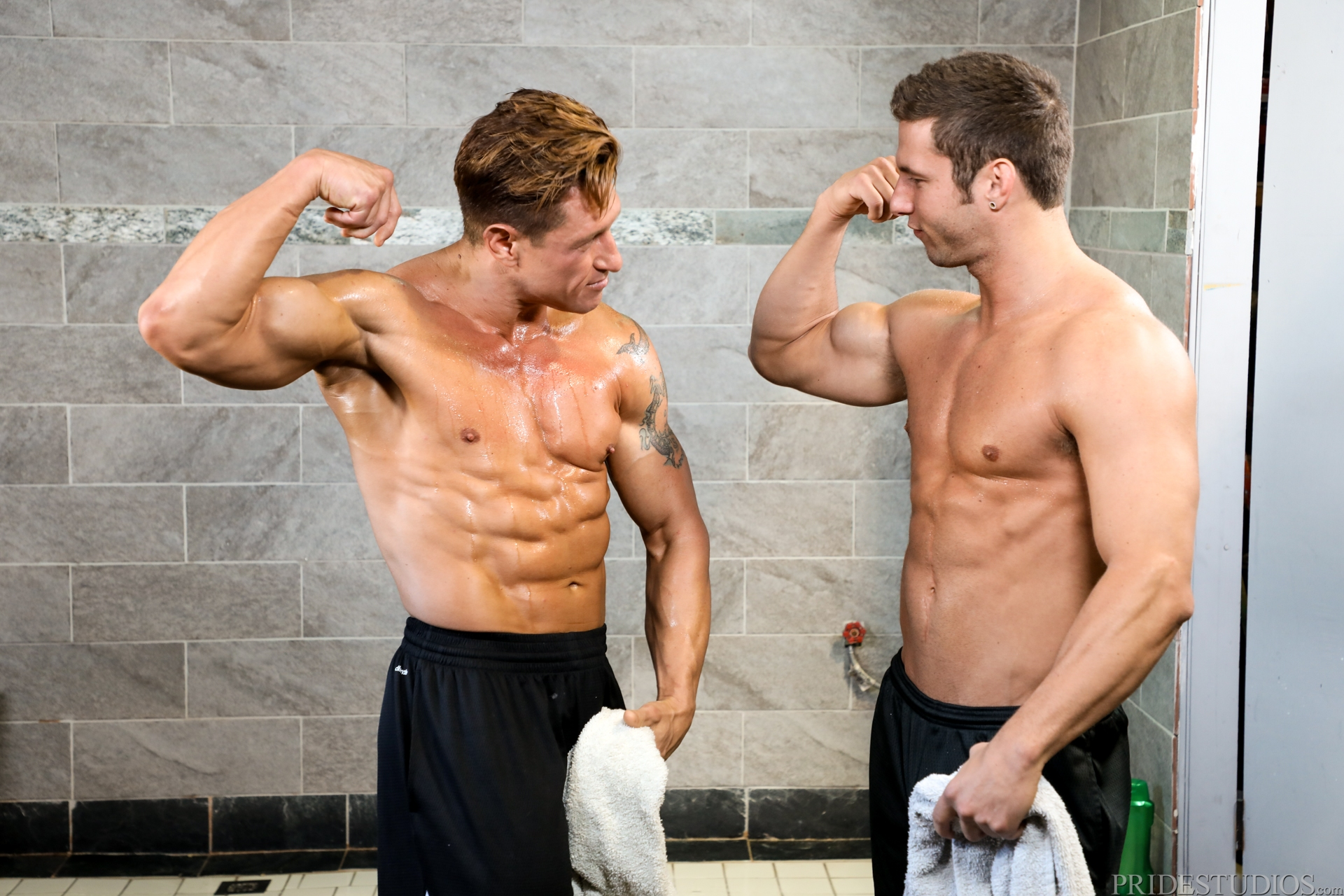 two muscled gym buddies comparing muscle in the showers