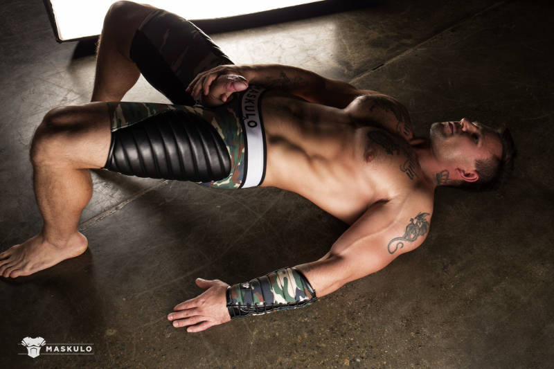 muscle man laying on the floor wearing Maskulo and jerking off