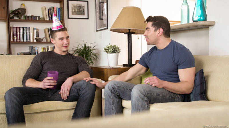 Two handsome men sitting on couches celebrating a birthday