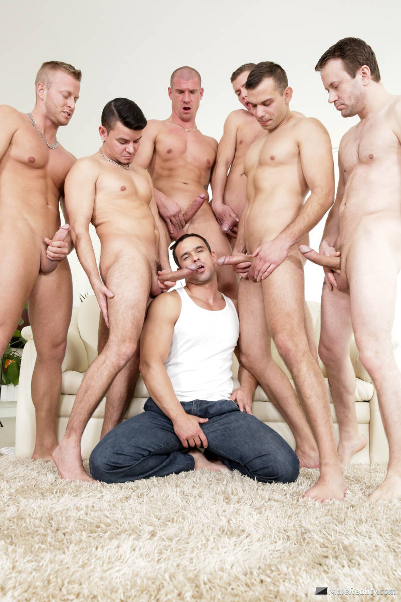 handsome muscled man kneeling on the floor and sucking six cocks