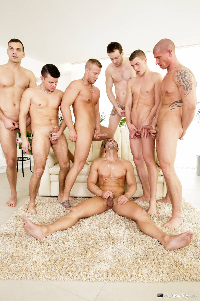 Muscle man jerking off while sitting on the floor as men cum over him