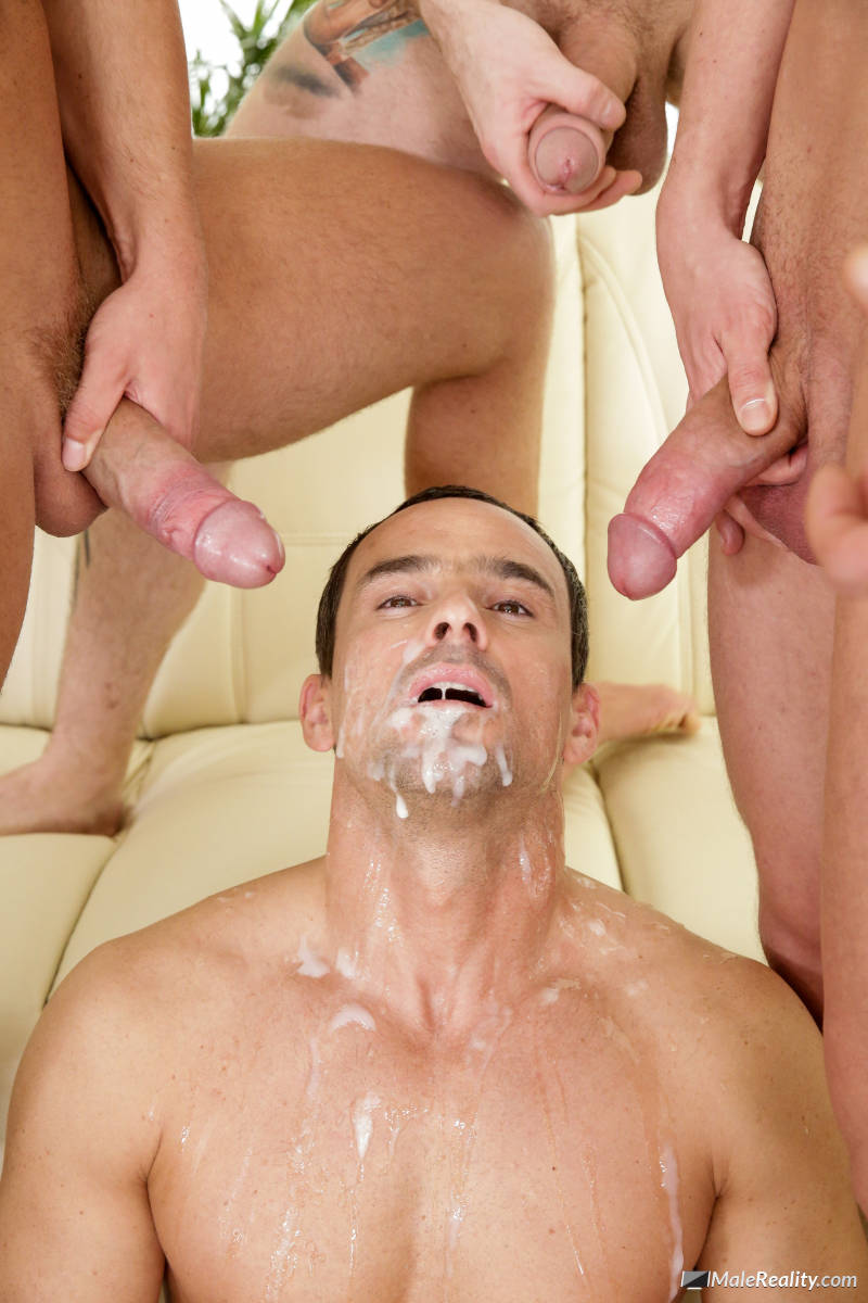 A handsome man lays back with two big cocks aiming at his face and cum all over his mouth and chin in a new gay bukkake video