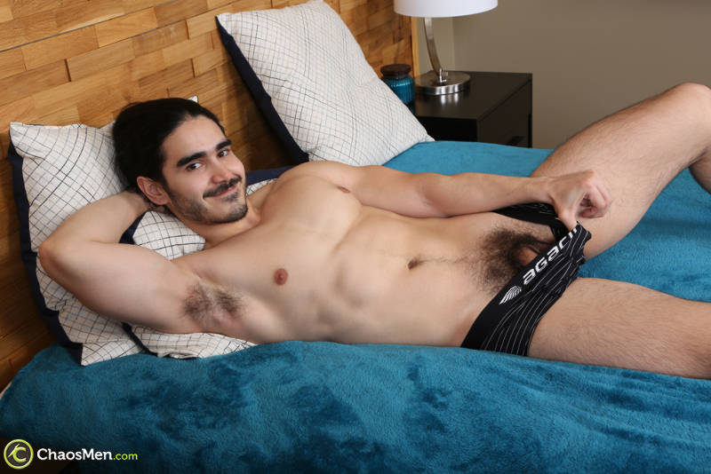Muscle man flashing his cock while laying on a bed