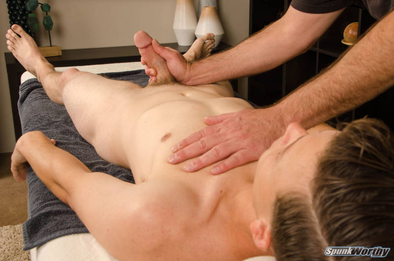 Straight guy laying on a massage table being jerked off by another man