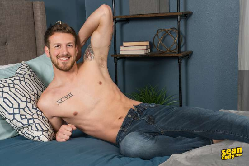 shirtless jock laying on a bed wearing jeans