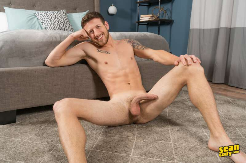 naked jock sitting on the floor with his legs apart showing a big cock and balls