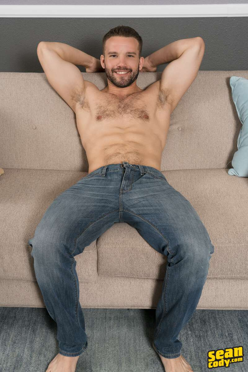 handsome shirtless jock wearing jeans and sitting on a couch