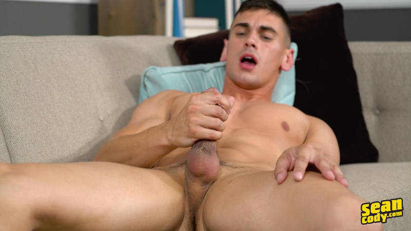 handsome muscle jock stroking his cock while laying on a couch