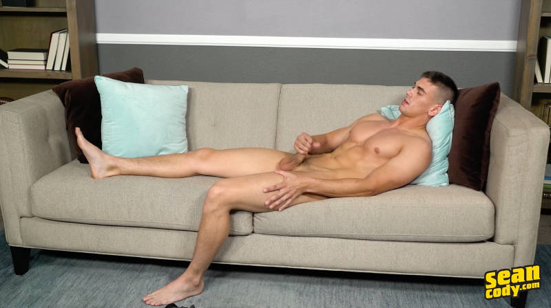 naked muscle jock laying on a couch and stroking his cock in a jerk off video for Sean Cody
