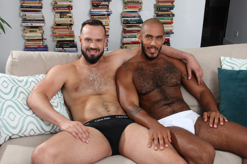 two hairy muscle men sitting on a couch for a bareback fuck flip flop